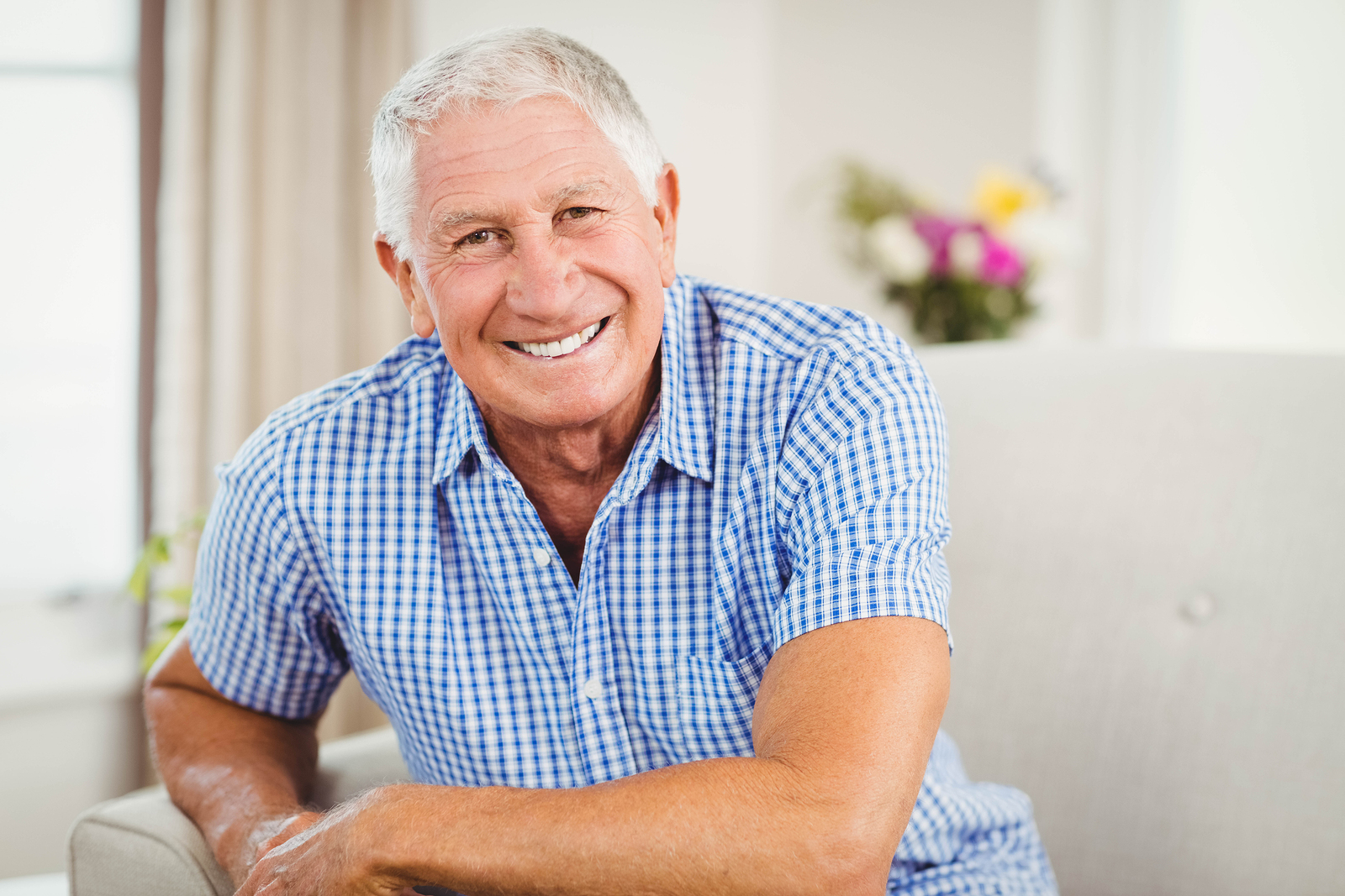 Image of senior man smiling in living room
